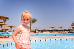 Smiling happy little blond girl at a resort pool Stock Images