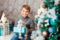 Smiling happy little boy sitting with christmas present near the chrismas tree. Smiling happy little boy sitting with christmas present   near the chrismas tree Stock Photos