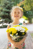 Smiling happy little girl with bouquet of flowers, summer outdoor.  Royalty Free Stock Image