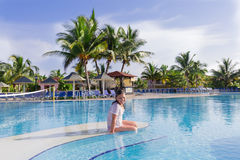 Smiling happy little girl sitting on the edge of swimming pool Royalty Free Stock Photography