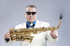 Smiling Happy Male Saxo Player in White Suit and Sunglasses Posi. Ng with Saxophone Against White Background.Horizontal Image Composition Stock Images
