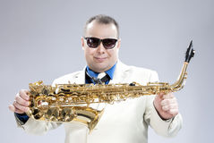Smiling Happy Male Saxo Player in White Suit and Sunglasses. Posing with Saxophone Against White Background.Horizontal Shot Stock Image