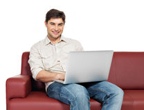 Smiling happy man with laptop sits on the divan. Portrait of smiling happy man with laptop sits on the divan, isolated on white Royalty Free Stock Photography