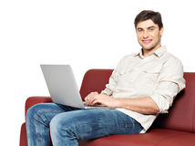 Smiling happy man with laptop sits on the divan. Portrait of smiling happy man with laptop sits on the divan, isolated on white Stock Photo