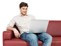 Smiling happy man with laptop sits on the divan Stock Image
