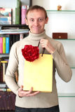 Smiling happy man presenting a gift with flower Stock Images