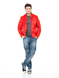 Smiling happy man in red jacket, blue jeans and gymshoes. Royalty Free Stock Image