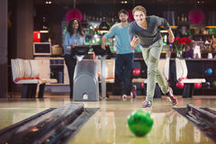 Smiling happy man is throwing the bowlingball Stock Images