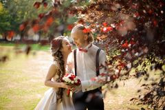Smiling married couple walking in a green park. Smiling and happy married couple walking in a green park with lawn and beautiful trees royalty free stock photography