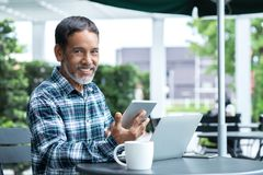 Smiling happy mature asian man with white stylish short beard using smartphone tablet serving internet at coffee shop cafe outdoor stock image