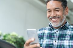 Smiling happy mature man with white stylish short beard using smartphone gadget serving internet. At coffee shop cafe outdoor. Laughing old man using social stock photos