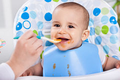 Smiling happy messy baby likes to eat Royalty Free Stock Images