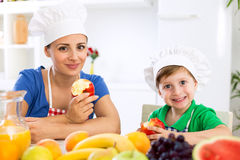 Smiling happy mother and child enjoy and eating fruits Stock Photo