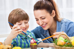 Smiling happy mother and child enjoy in painting easter eggs Stock Images