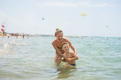 Smiling and happy mother and her son playing and running on the beach. Concept of friendly family. Boy woman Stock Image