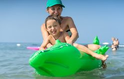 Smiling happy mother and son playing on the wave in the sea in the daytime. Happy family relaxing by the sea. Summer, spring and w Stock Photo