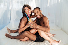 Smiling happy multiracial couple sitting and drinking at the beach Stock Photography