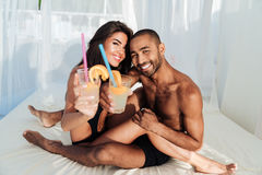 Smiling happy multiracial couple sitting and drinking at the beach Royalty Free Stock Images