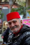 Smiling happy old Turkish man in fez and leather jacket. Istanbul, Turkey - March 16, 2015: A portrait of a senior man who works outside a church museum as a stock photo