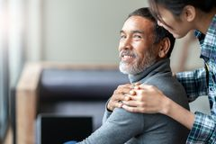 Free Smiling Happy Older Asian Father With Stylish Short Beard Touching Daughter`s Hand On Shoulder Looking Royalty Free Stock Photos - 125087328