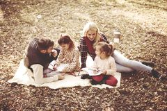 Happy parents with daughter in park and writing together stock photography