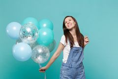 Smiling happy pensive young woman in denim clothes looking up celebrating and holding colorful air balloons isolated on