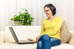 Smiling happy person sofa shopping online laptop Royalty Free Stock Photo