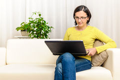 Smiling happy person sofa shopping online laptop Stock Image