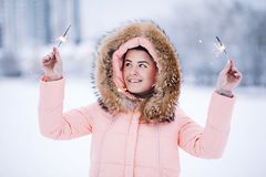 Smiling happy pretty woman in warm winter jacket outdoors enjoys winter journey, weared gloves and hood, a lot of snow. Smiling pretty woman in warm winter Stock Photos