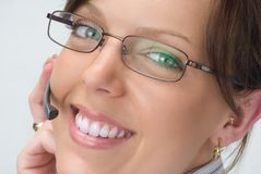 Smiling Happy Receptionist. A smiling happy receptionist with telephone headset. She has beautiful flawless skin and teeth. Her smile greets customers and she is stock photos