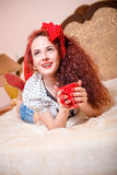 Smiling happy red head lady daydreaming with cup Royalty Free Stock Photography