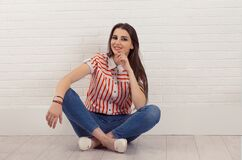 Smiling Happy. Relaxed Happy Young Woman Sat Cross-legged On Floor, Touching Chin, Looking At Camera, Isolated White Brick Wall Royalty Free Stock Images
