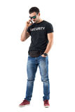 Smiling happy relaxed undercover policeman talking on the phone looking down. Full body length portrait isolated on white studio background Royalty Free Stock Photos