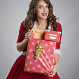 Smiling happy Santa helper girl carrying pile of various gift boxes Stock Photos