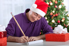 Smiling happy senior man writes wishes to santa claus Royalty Free Stock Image