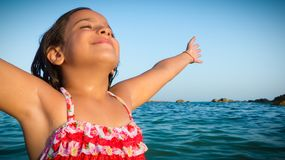 Smiling, happy and serene young girl embracing sun rays stock photos