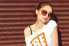 Smiling happy sexy girl sitting near the wall in sunglasses redhead with big full lips Stock Image