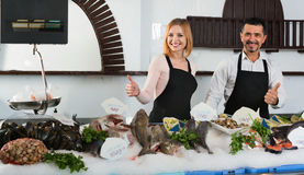 Smiling happy shop assistants selling fresh fish Stock Photo