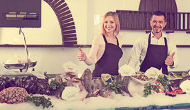 Smiling happy shop assistants selling fresh fish. And chilled seafood royalty free stock photos