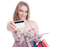 Smiling happy shopaholic with tablet offer debit card Royalty Free Stock Photos