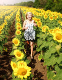 Smiling happy teenage girl runs in field of sunflowers Royalty Free Stock Image