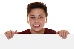 Smiling happy teenager boy looking behind an empty banner with c. Opyspace, isolated on a white background Royalty Free Stock Photo