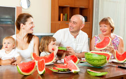 Smiling happy three generations family eating watermelon  over Stock Images