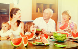 Smiling happy three generations family eating watermelon  over Royalty Free Stock Image