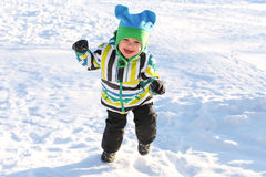 Smiling happy toddler running in winter outdoors Royalty Free Stock Photo