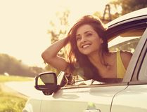 Smiling happy traveling young woman looking from the new car win. Dow on summer bright green nature background. Toned closeup portrait