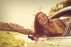 Smiling happy traveling young woman looking from the new car win stock photo