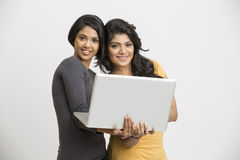 Smiling happy two young women with laptop Stock Image