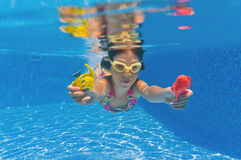 Smiling happy underwater kid in swimming pool Royalty Free Stock Photos
