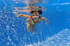 Smiling happy underwater kid in swimming pool Royalty Free Stock Images